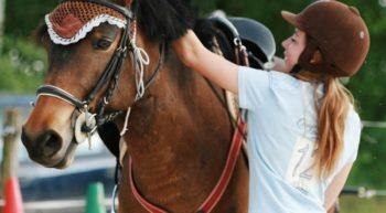 La cavalière de Naya des Landes ressert sa selle avant une séance d'entraînement